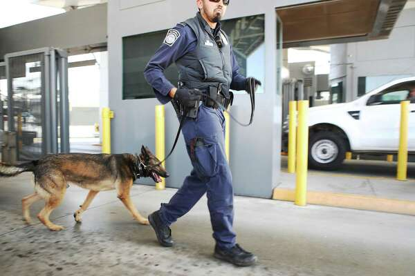 A Customs and Border Protection officer, with his dog, walks to inspect vehicles entering the United States at the port of entry from Mexico in San Ysidro (San Diego County).