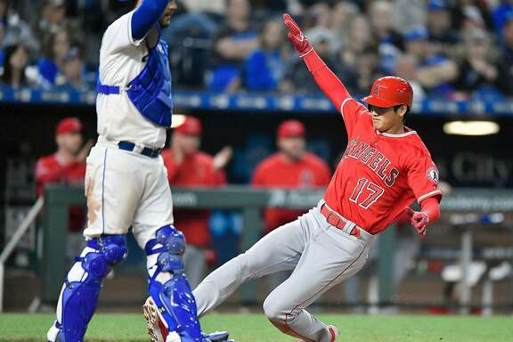 The Los Angeles Angels' Shohei Ohtani scores in front of Kansas City Royals catcher Drew Butera on a sacrifice fly by Ian Kinsler in the eighth inning on Friday, April 13, 2018, at Kauffman Stadium in Kansas City, Mo. The Angels won, 5-4. (John Sleezer/Kansas City Star/TNS)