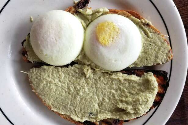 """Eggs """"Rose"""" (poached eggs on top of toasted Kalamata sourdough bread slathered with artichoke spread) costs $16 at D'Angelo Bread."""