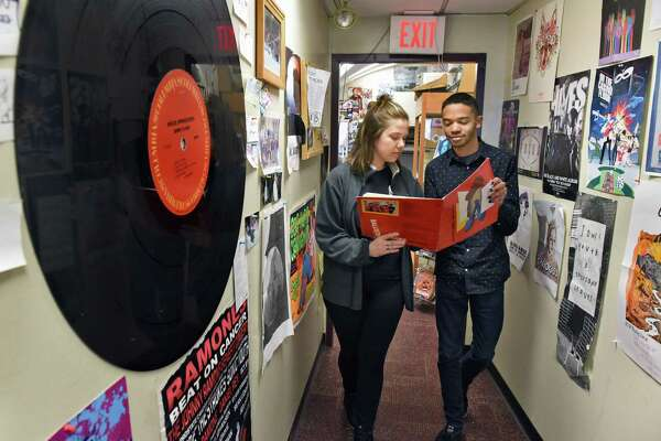WCDB DJ Jon, Gen Roberts, left, and DJ Pink, Kirk Kitson UAlbany's check out an old record album in the offices of the campus radio station Friday April 13, 2018 in Albany,NY. (John Carl D'Annibale/Times Union)