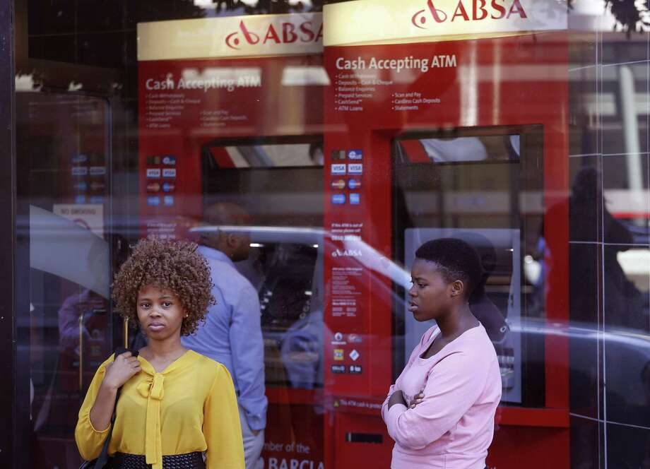 In this March 1, 2016, file photo, two women stand outside a building used by South Africa's ABSA bank in Cape Town, South Africa. Roughly seven out of every 10 adults worldwide now has some form of a bank account, the World Bank said Thursday, April 19, fueled largely by the proliferation of cell phone-based bank accounts and other simple bank account programs in places like India and Sub-Saharan Africa. Photo: Schalk Van Zuydam /Associated Press / Copyright 2018 The Associated Press. All rights reserved.