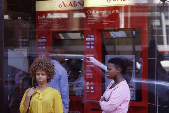 In this March 1, 2016, file photo, two women stand outside a building used by South Africa's ABSA bank in Cape Town, South Africa. Roughly seven out of every 10 adults worldwide now has some form of a bank account, the World Bank said Thursday, April 19, fueled largely by the proliferation of cell phone-based bank accounts and other simple bank account programs in places like India and Sub-Saharan Africa.