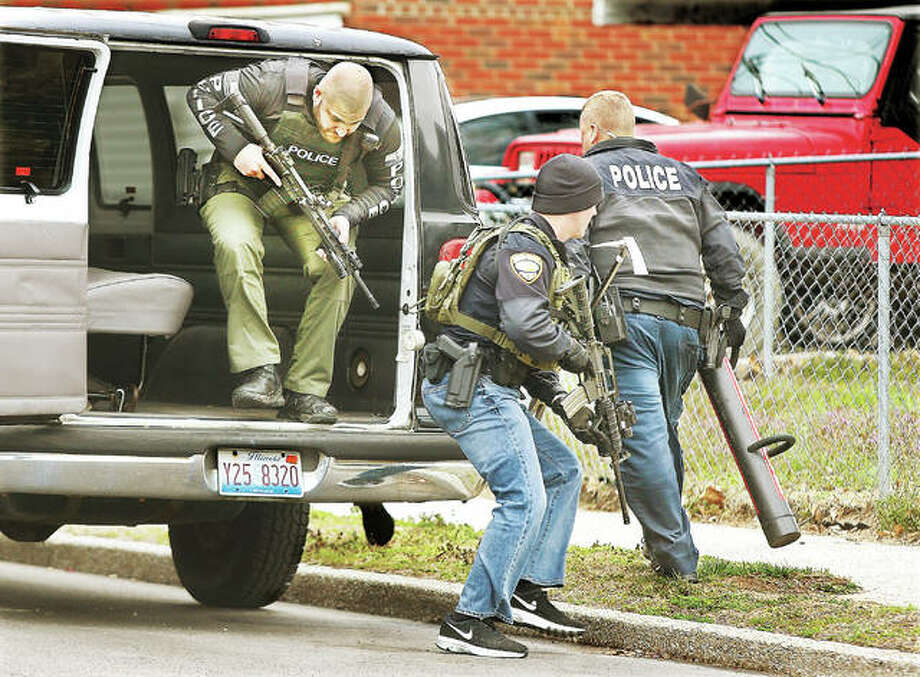 Heavily armed Wood River police officers from the city's drug unit leap from the back of a vehicle to carry out a search warrant early Thursday morning in an apartment unit at 476 Hamilton Ave. in Wood River that resulted in two felony arrests. Officers arrested a female suspect as she left the apartment, and ordered a male in an upstairs apartment to open his door several times before using a battering ram to gain entry. The raids are part of a continuing crackdown on drug sales in the city. The charges on both individuals were enhanced because of their proximity to a city park. Photo:       John Badman|The Telegraph