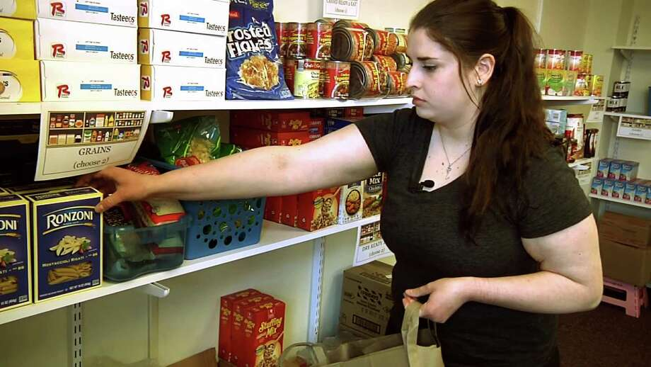 In this April 10, 2018 frame grab from video, student Hannah Daignault fills a grocery bag at the Schenectady County Community College food pantry in Schenectady, N.Y. As a 22-year-old student living on her own, Daignault finds it hard to stretch her student loans to cover the rising cost of books and fees, let alone food and rent, so she was thrilled when a campus food pantry opened last year. New York is the nation's first state to require free food pantries on all its public college campuses. Photo: Michael Hill /Associated Press / Copyright 2018 The Associated Press. All rights reserved.