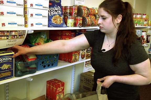 In this April 10, 2018 frame grab from video, student Hannah Daignault fills a grocery bag at the Schenectady County Community College food pantry in Schenectady, N.Y. As a 22-year-old student living on her own, Daignault finds it hard to stretch her student loans to cover the rising cost of books and fees, let alone food and rent, so she was thrilled when a campus food pantry opened last year. New York is the nation's first state to require free food pantries on all its public college campuses.