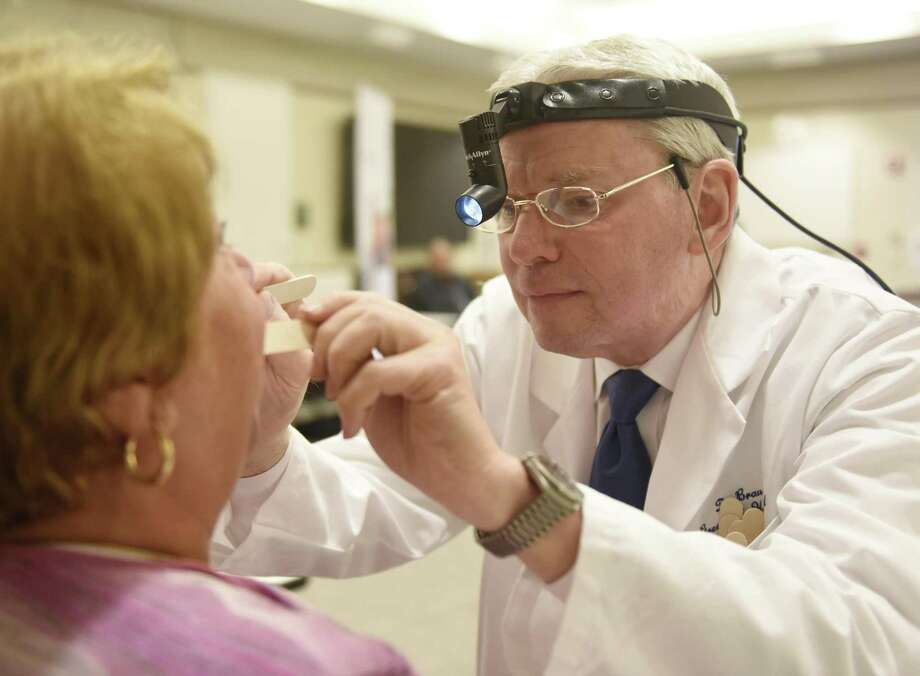 Dr. Richard Brauer, Chief of Otolaryngology at Greenwich Hospital, performs a free head and neck cancer screening to Brigitte Foscante at Greenwich Hospital in Greenwich. Dr. Brauer has seen an increasing number of patients with HPV-positive cancer of the tongue and tonsils and believes children and adults should consider getting the HPV vaccine. Photo: Tyler Sizemore / Hearst Connecticut Media / Greenwich Time