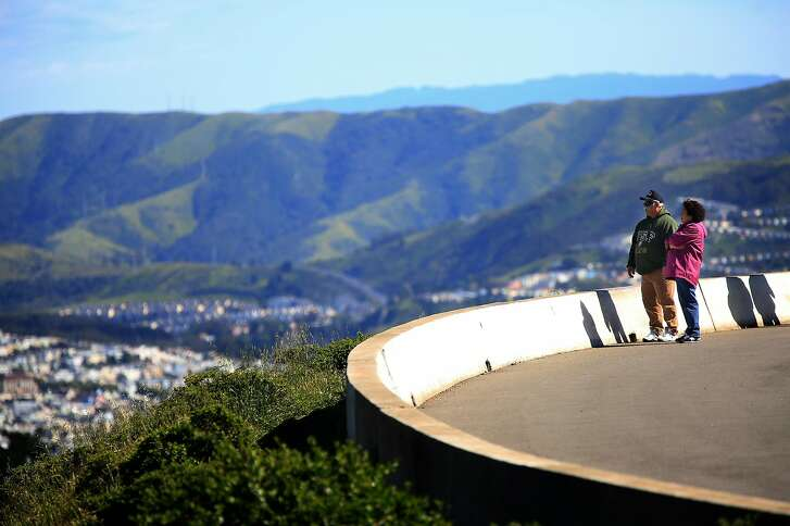 Serf Rodriquez (l to r) and Maggie Rodriquez, both of Seattle, WA.  take in the view from atop Twin Peaks while enjoying a walk along half of the figure-eight road at the top of Twin Peaks which has been closed during a pilot program on Wednesday,  April 18, 2018, in  San Francisco, Calif.