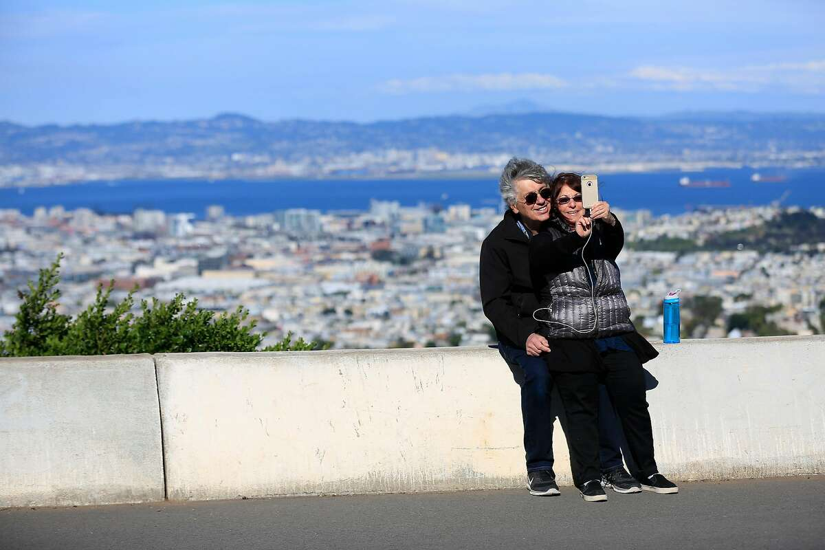 Bob (l to r) and Mona Small of Philadelphia, PA. take a picture of themselves while enjoying a walk along half of the figure-eight road at the top of Twin Peaks which has been closed during a pilot program on Wednesday, April 18, 2018, in San Francisco, Calif.