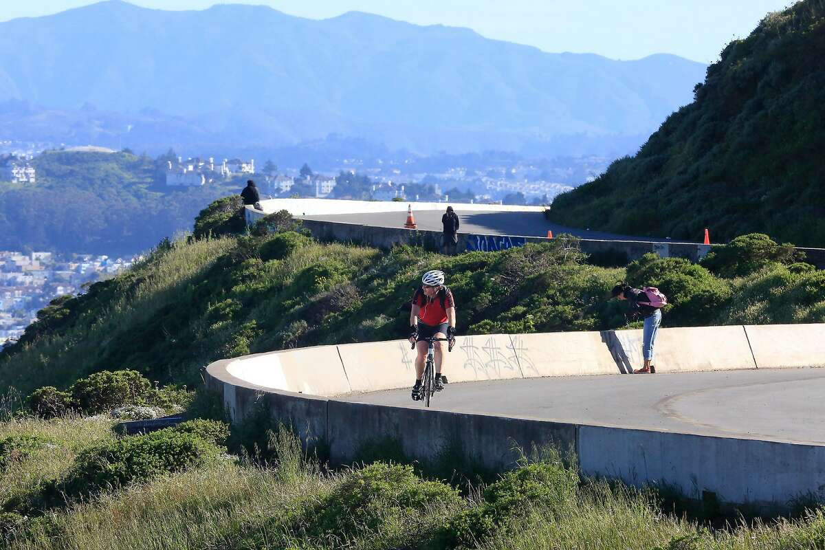 Cyclists and pedestrians ride and walk along half of the figure-eight road at the top of Twin Peaks which has been closed during a pilot program on Wednesday, April 18, 2018, in San Francisco, Calif.