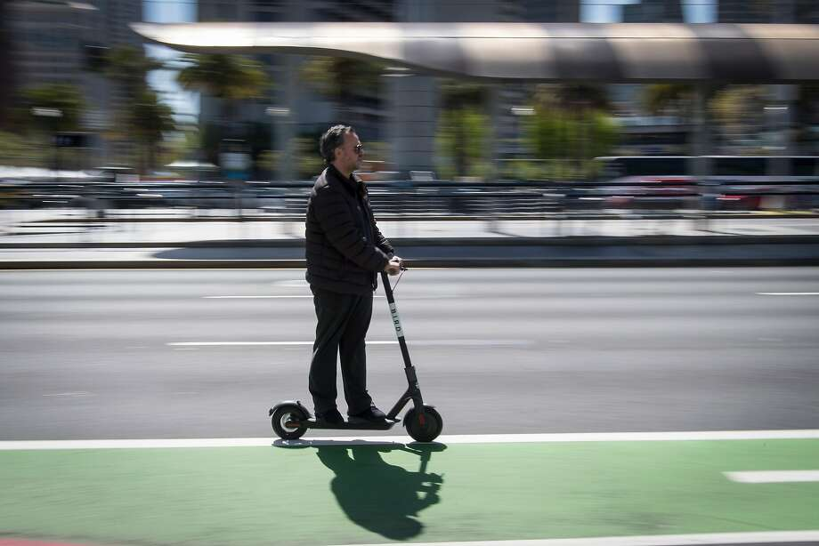 A person rides a Bird Rides Inc. shared electric scooter on the Embarcadero in San Francisco on Friday, April 13, 2018. GPS-enabled scooters and bicycles are spreading across several major U.S. cities, driven by a wave of venture capital into a handful of companies. Photo: David Paul Morris / Bloomberg