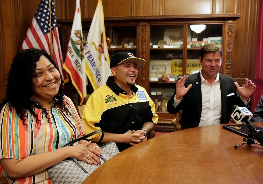 Alberto Carrillo (center), with his wife, Francisca Carrillo, is honored by Mayor Mark Farrell for actions in rescuing a man who overdosed and another suffering from dehydration. Photo: Michael Macor / The Chronicle