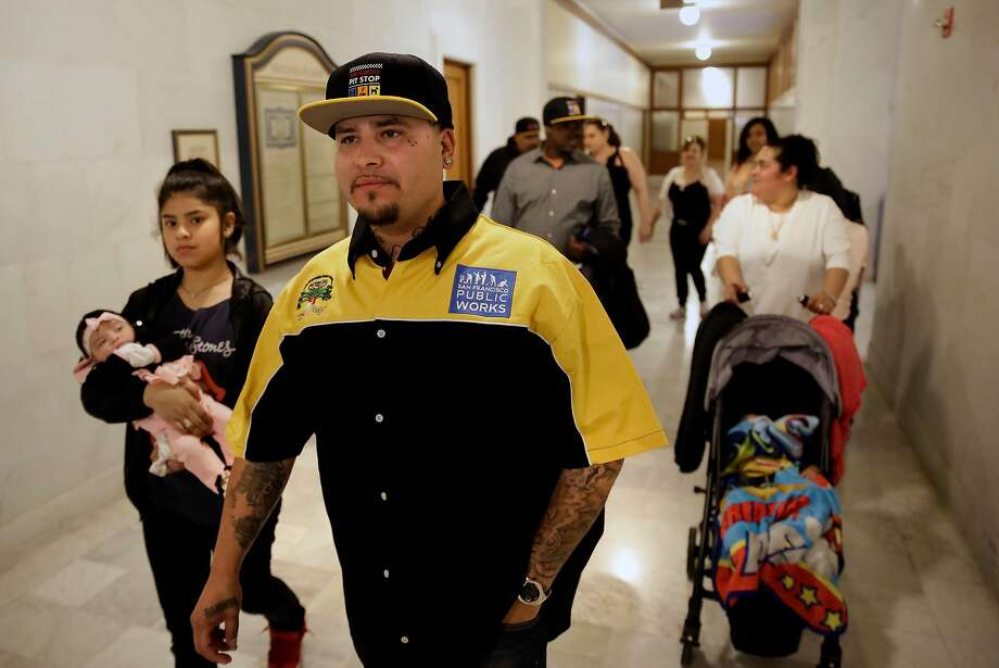 Alberto Carrillo, with public works walks to the the office of the Mayor of San Francisco Mark Farrell, with his family along at City Hall in San Francisco, Calif., on Thurs. April 19, 2018, to be honored for saving the lives of two people last month,  Carrillo who works as Pitstop monitor, a bathroom area provided by public works, where he rescued one man from a drug overdose and another who was suffering from heart attack in the Tenderloin. Photo: Michael Macor / The Chronicle