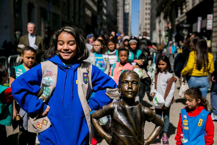 "Girl Scouts stand with the ""Fearless Girl"" statue a year ago. New York Mayor Bill de Blasio said the statue will be moved from its spot on Broadway. Photo: Sam Hodgson / New York Times 2017"