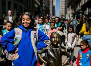 """FILE — Girl Scouts with the """"Fearless Girl"""" statue in Lower Manhattan, April 13, 2017. New York Mayor Bill de Blasio said on April 19, 2018, that the statue would be moved from its spot on Broadway to one facing the New York Stock Exchange; """"Charging Bull"""" may soon follow. (Sam Hodgson/The New York Times)"""