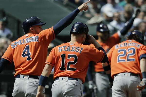 Houston Astros' George Springer (4), Max Stassi (12), and Josh Reddick (22) walk to the dugout after they scored on a three-run double hit by Jose Altuve during the fifth inning of a baseball game against the Seattle Mariners, Thursday, April 19, 2018, in Seattle. (AP Photo/Ted S. Warren)
