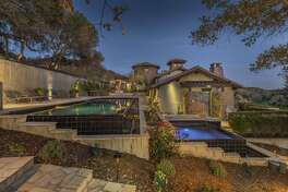 The sloping landscape at 5722 Cottage Ridge Road in Santa Rosa features a pool and hot tub.