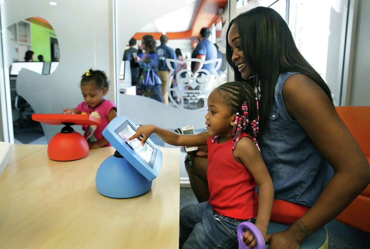 Oaisha Louis, right, plays a computer game with her daughter Rau'mari Kirkland in the Harvey E. Najim Family Foundation Children's Area at the grand opening of East Side Bibliotech named after Dr. E. Thurman Walker Jr., on Thursday, April 19, 2018.