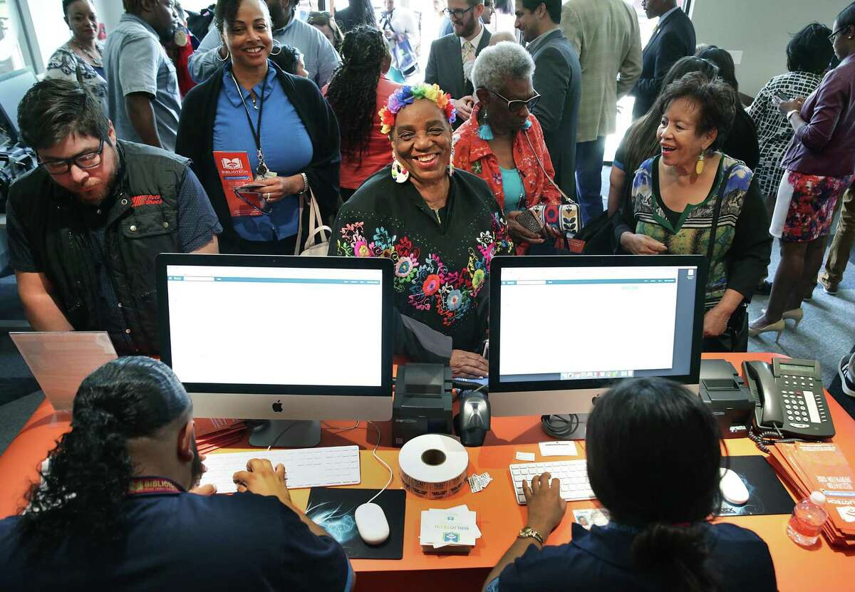 Bibliotech workers sign up visitors for their online library cards during the grand opening of East Side Bibliotech named after Dr. E. Thurman Walker Jr., on Thursday, April 19, 2018.