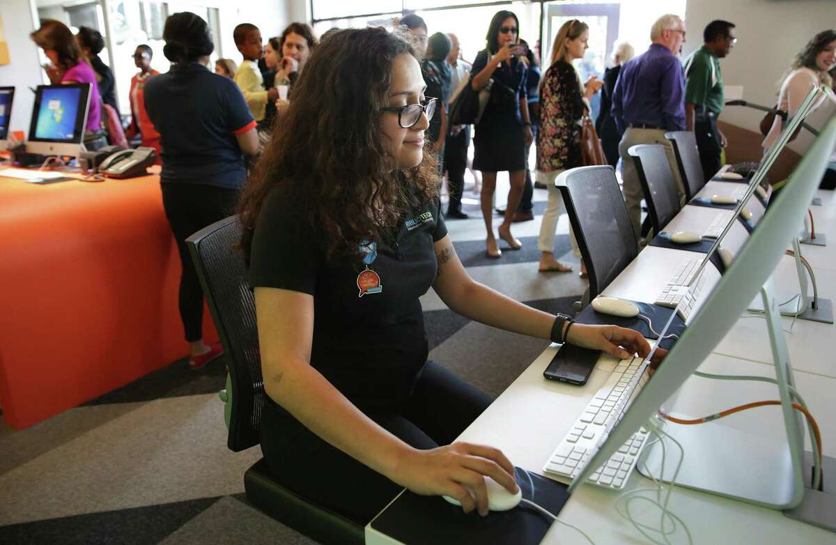 Jessica Calderon, tech support specialist, sets up computers at the grand opening of East Side BiblioTech in 2018. BiblioTech, which opened in 2013 as the nation's first all-digital public library system, is offering curbside pickup of portable devices during the pandemic, starting Tuesday.