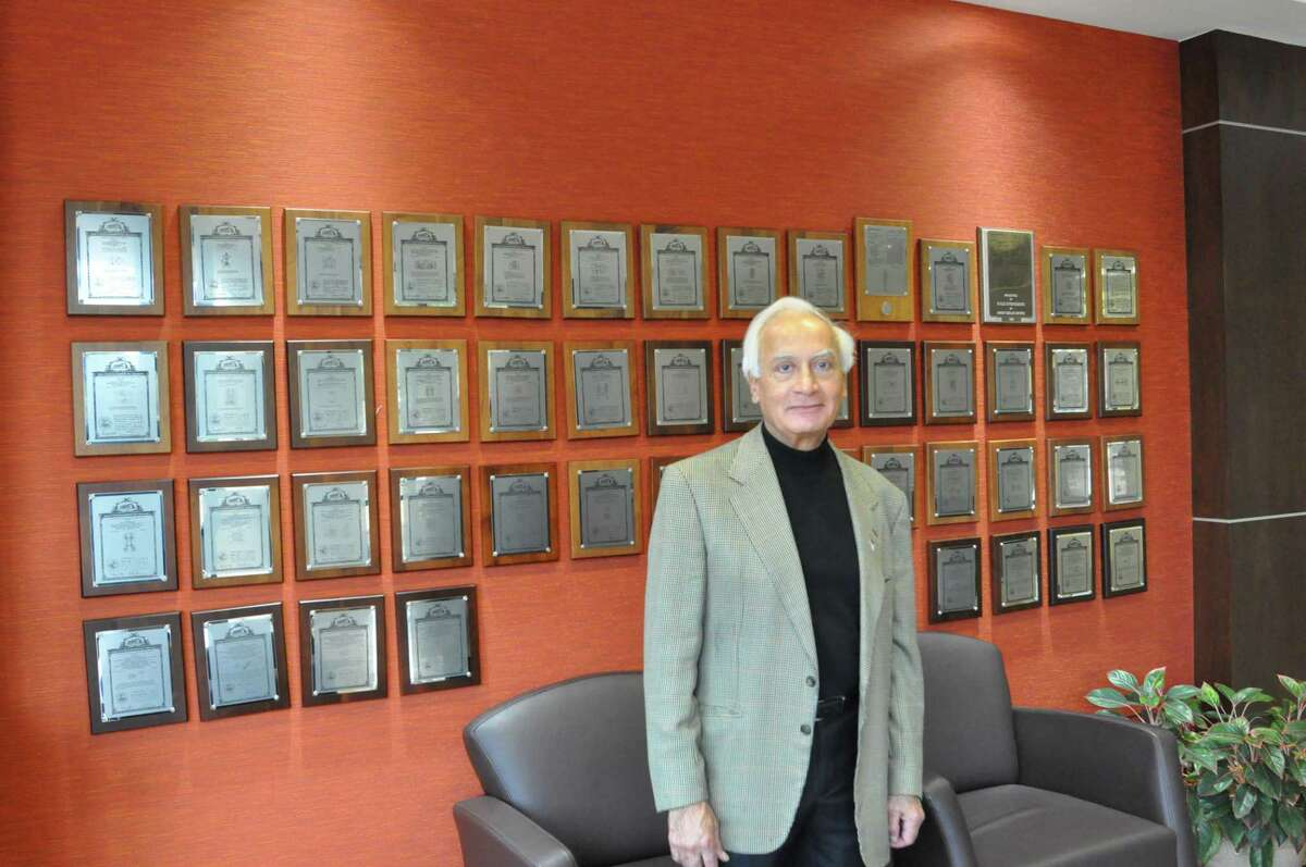 M.S. Kalsi, founder of Kalsi Engineering, stands in front of plaques commemorating the 50 patents his firm has recorded since it opened in 1978.