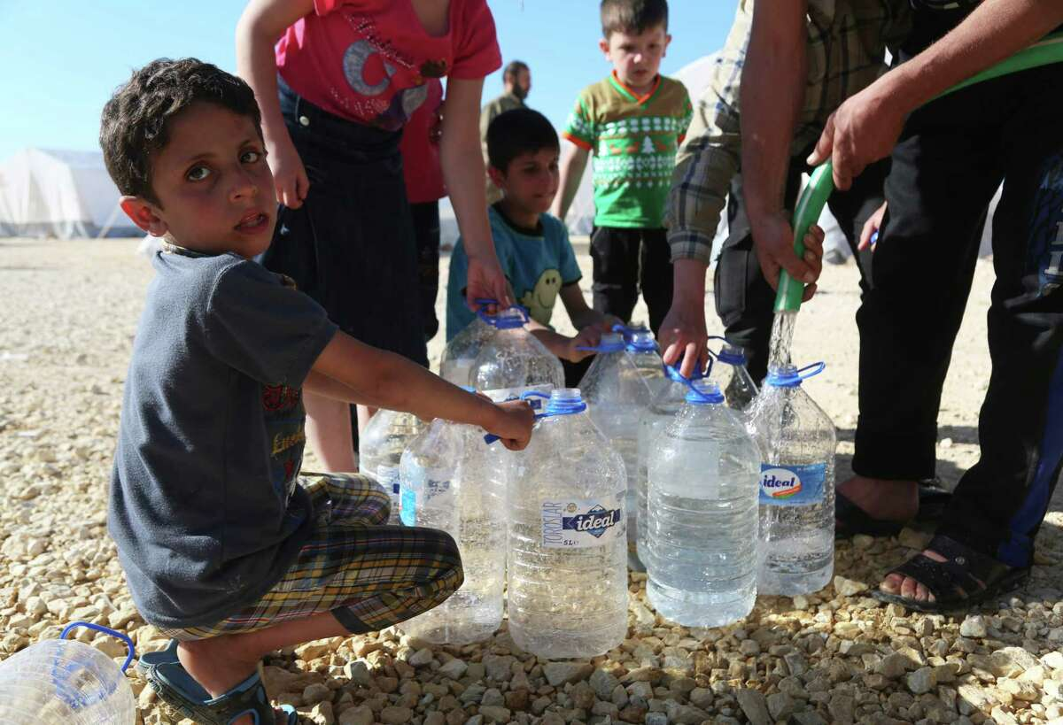 Children fill water containers at a camp for displaced Syrians in al-Bil, east of the rebel-held town of Azaz in northern Syria, on April 15, 2018. / AFP PHOTO / Zein Al RIFAIZEIN AL RIFAI/AFP/Getty Images