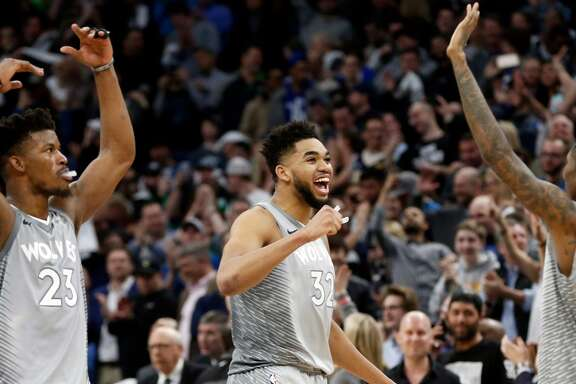 Minnesota Timberwolves' Jimmy Butler, left, Karl-Anthony Towns, center and Jamal Crawford celebrate in the final seconds as the Timberwolves defeated the Denver Nuggets 112-106 in overtime in an NBA basketball game Wednesday, April 11, 2018, in Minneapolis. The Timberwolves advanced to the playoffs for the first time in 14 years. (AP Photo/Jim Mone)