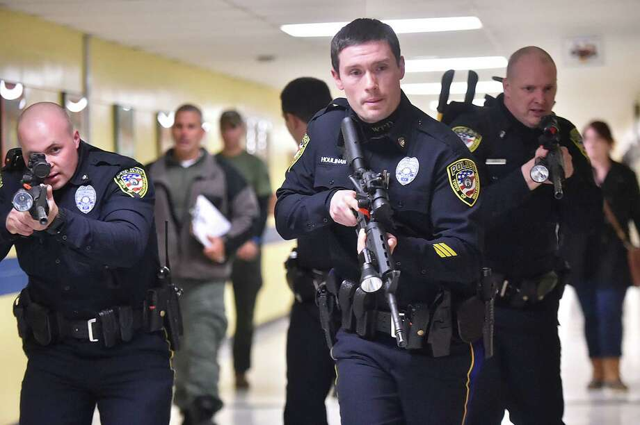 Detective Sean Houlihan, center, front center, Detective Stephen Jacques, left, and Patrolman Andrew Stolfi, at right, members of the Wallingford Police Department participate in an active shooter training, Thursday, April 19, 2018, during April vacation at Moran Middle School at 141 Hope Hill Road in Wallingford. Photo: Catherine Avalone, Hearst Connecticut Media / New Haven Register