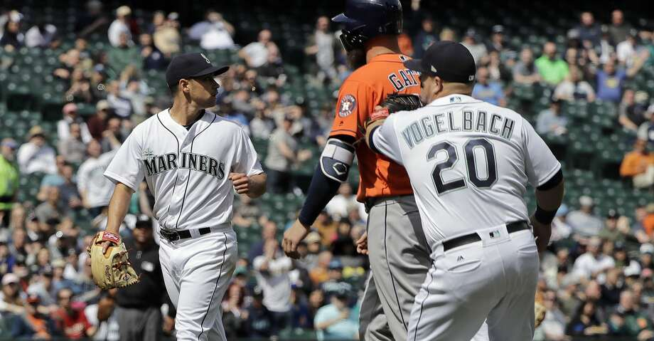 Seattle Mariners first baseman Daniel Vogelbach (20) tags out Houston Astros' Evan Gattis, second from right, for the third out of a triple play as Mariners' starting pitcher Marco Gonzales, left, looks on after Gattis left first base and started walking to the dugout after the first two outs during the fourth inning of a baseball game, Thursday, April 19, 2018, in Seattle. (AP Photo/Ted S. Warren) Photo: Ted S. Warren/Associated Press