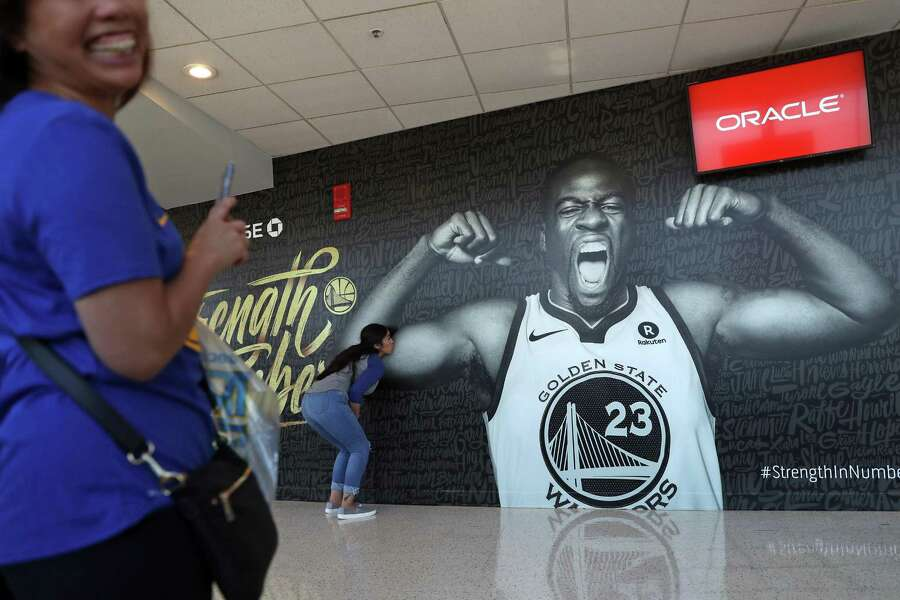 Golden State Warriors' fan Natalie Palos of Corning kisses Draymond Green's bicep on a mural in the upper concourse at Oracle Arena before the Warriors play San Antonio Spurs in Game 1 of NBA Western Conference First Round playoff game in Oakland, Calif., on Saturday, April 14, 2018. Photo: Scott Strazzante / The Chronicle / San Francisco Chronicle