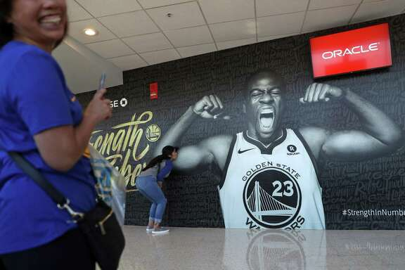 Golden State Warriors' fan Natalie Palos of Corning kisses Draymond Green's bicep on a mural in the upper concourse at Oracle Arena before the Warriors play San Antonio Spurs in Game 1 of NBA Western Conference First Round playoff game in Oakland, Calif., on Saturday, April 14, 2018.