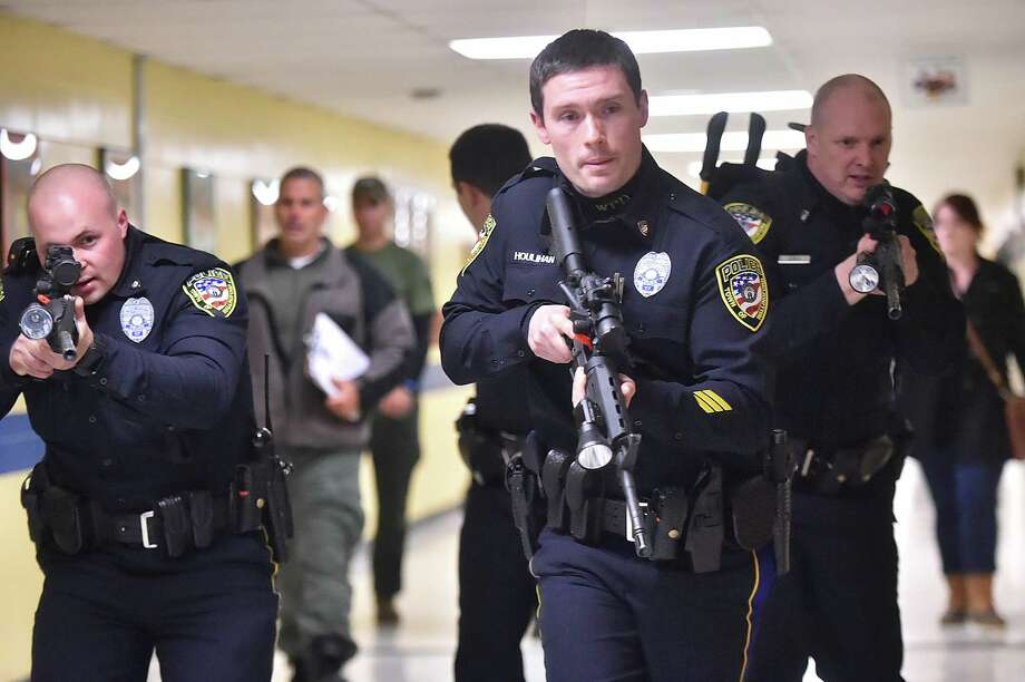 Wallingford police Detective Sean Houlihan, front center, Detective Stephen Jacques, left, and Patrolman Andrew Stolfi, right, participate in an active shooter training Thursday at Moran Middle School in Wallingford. Photo: Catherine Avalone / Hearst Connecticut Media / New Haven Register