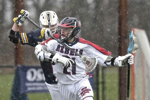 New Fairfield's Brett Tenaglia (21) is held up by Weston's Jason Baisley (1) as he brings the ball up field in the boys lacrosse game between Weston and New Fairfield high schools, Thursday, April 19, 2018, at New Fairfield High School, New Fairfield, Conn.