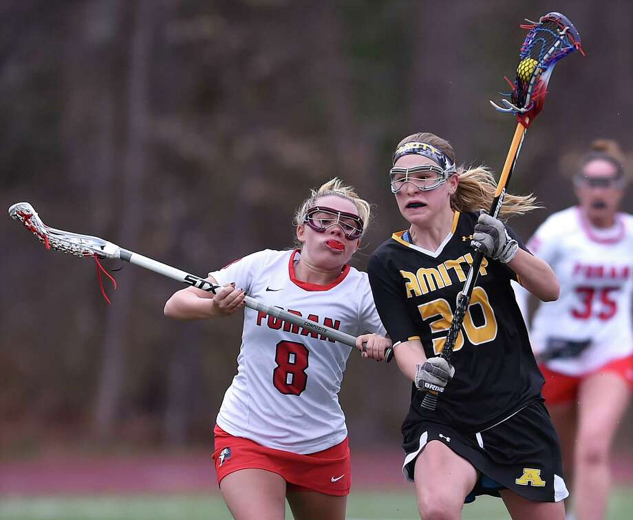 Foran midfielder Emily Kwalek battles Amity's Ana Carney at Vito DeVito Sports Complex, Thursday, April 19, 2018, at Foran High School in Milford. Amity won, 16-14, Photo: Catherine Avalone, Hearst Connecticut Media / New Haven Register
