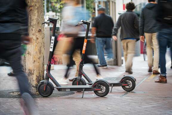 Pedestrians walk past a Bird Rides Inc., left, and Skinny Labs Inc. SpinBikes shared electric scooters parked on Market Street in San Francisco, California, U.S., on Friday, April 13, 2018. GPS-enabled scooters and bicycles are spreading across several major U.S. cities, driven by a wave of venture capital into a handful of companies. Policymakers are scrambling to find ways to regulate the great scooter boom of 2018. Photographer: David Paul Morris/Bloomberg