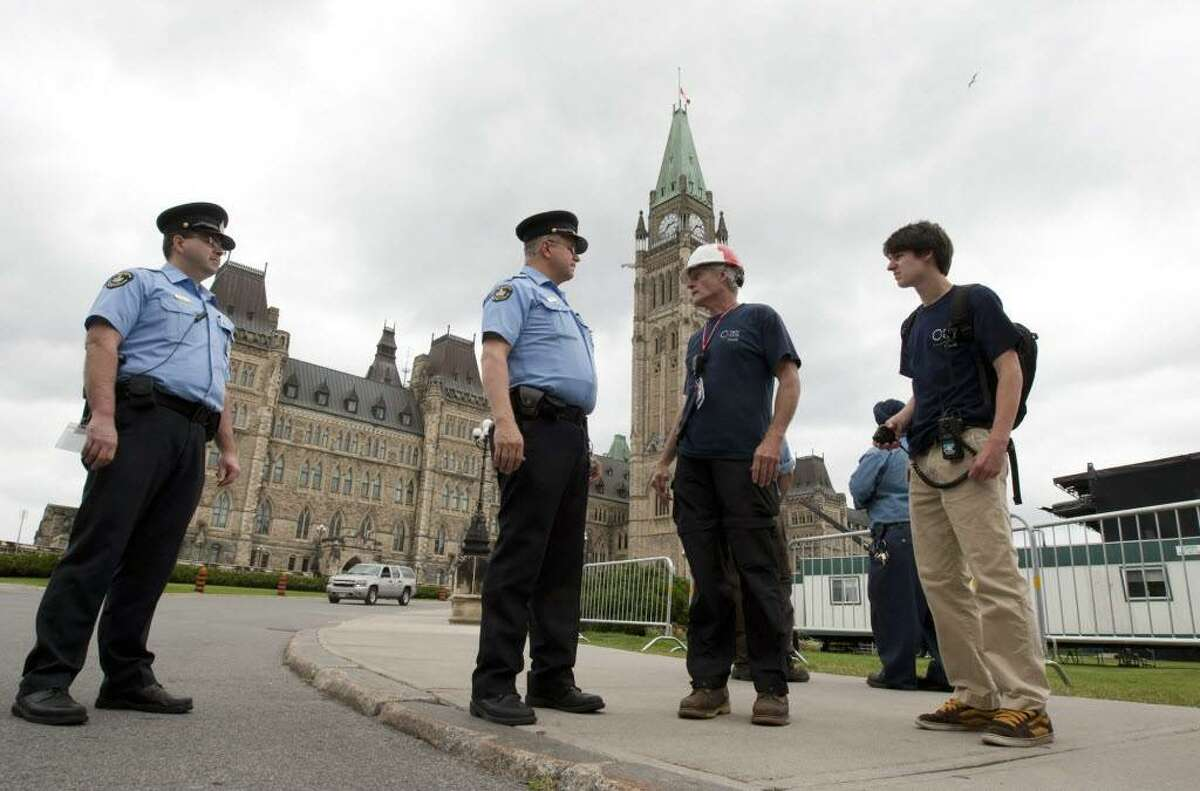 Parliamentary security guards stop construction workers from returning to their work site after Parliament buildings were evacuated following an earthquake in Ottawa, Canada on Wednesday June 23, 2010. A magnitude-5.0 earthquake struck at the Ontario-Quebec border region of Canada on Wednesday, shaking homes and businesses from Toronto to the states of New York and Michigan, according to the U.S. Geological Survey. (AP Photo/The Canadian Press, Adrian Wyld)