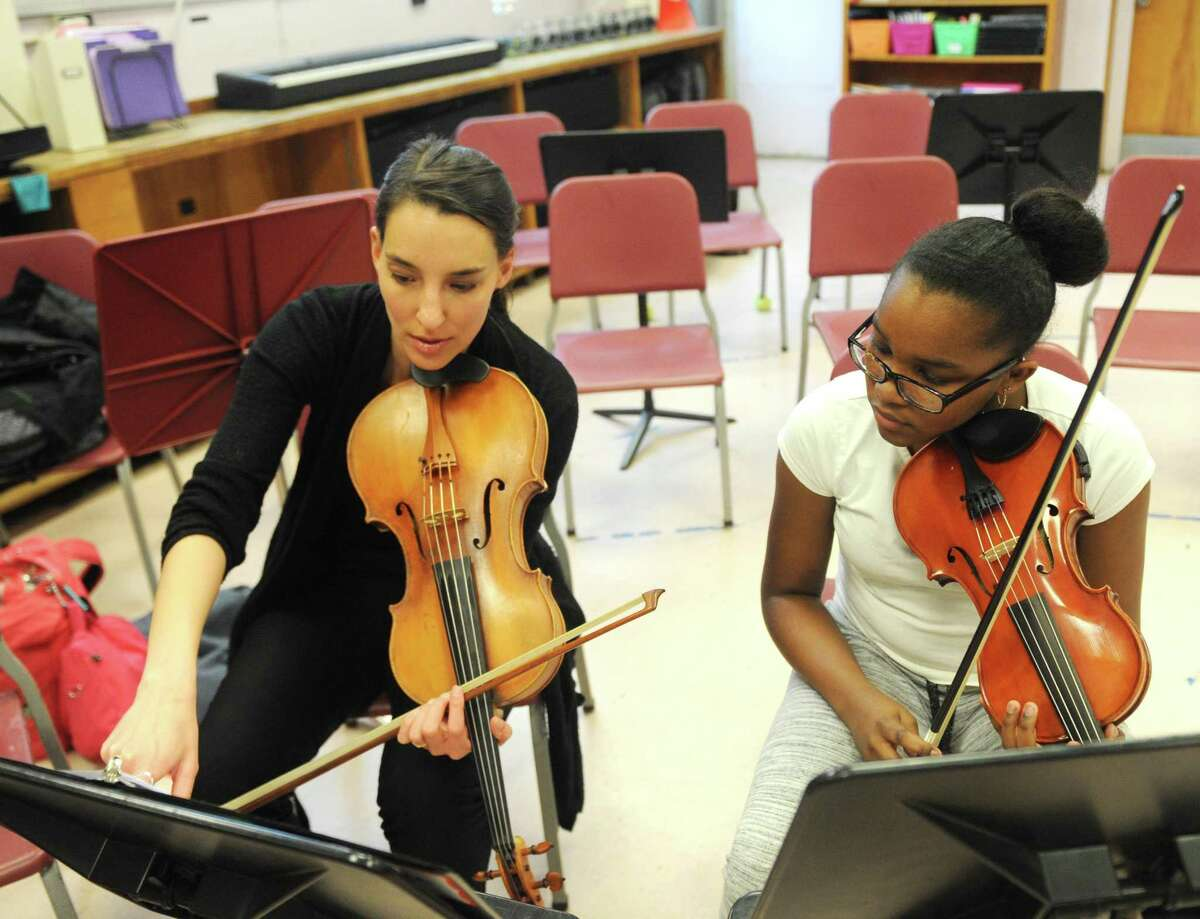 Greenwich Symphony viola player Nora Krohn teaches sixth-grader Jada Brewington during Greenwich Alliance for Education?'s Tuning In To Music free lesson at Western Middle School in Greenwich, Conn. Tuesday, April 19, 2018. Members of the Greenwich Symphony taught group lessons to kids in grades four through 12. Students learned three songs and put on a performance for parents and teachers at the end.