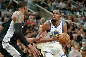 Golden State Warriors' Draymond Green (23) and Kevon Looney (5) defend against a drive to the basket by San Antonio Spurs' Manu Ginobili, center, during the first half of Game 3 of a first-round NBA basketball playoff series in San Antonio, Thursday, April 19, 2018. (AP Photo/Eric Gay)