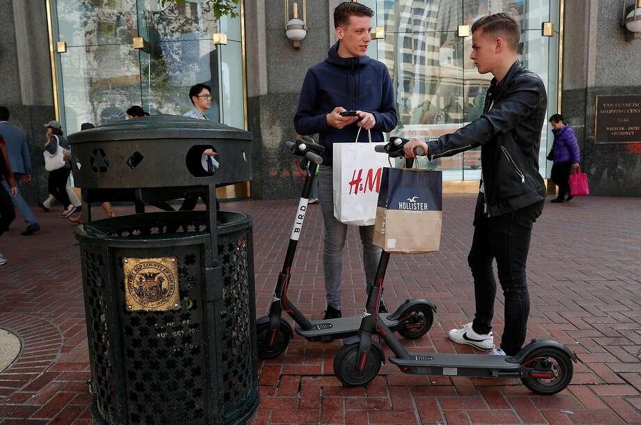Leo Dubler (left) and Bastien Ruch, visiting from Switzerland, check out two Bird scooters on Market Street in San Francisco. Photo: Michael Macor / The Chronicle