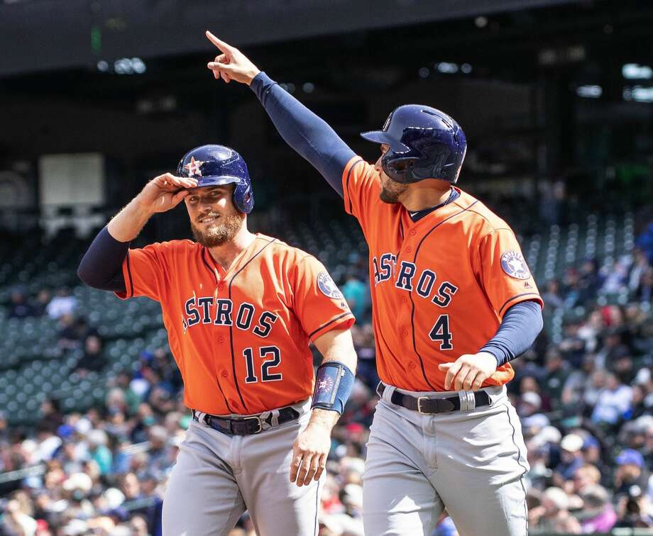 The Houston Astros' George Springer (4) salutes Jose Altuve after he scored on Altuve's bases-loaded double in the fifth inning against the Seattle Mariners on Thursday, April 19, 2018, at Safeco Field in Seattle. The Astros won, 9-2. (Dean Rutz/Seattle Times/TNS) Photo: Dean Rutz/TNS