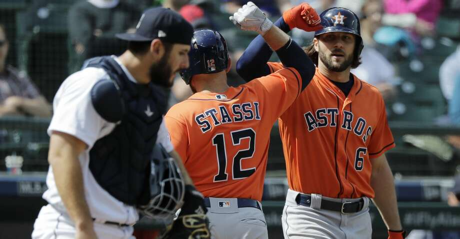Houston Astros' Max Stassi (12) is greeted at the plate by Jake Marisnick, right, as Seattle Mariners catcher David Freitas, left, looks on after Stassi hit a solo home run during the seventh inning of a baseball game, Thursday, April 19, 2018, in Seattle. (AP Photo/Ted S. Warren) Photo: Ted S. Warren/Associated Press