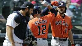 Houston Astros' Max Stassi (12) is greeted at the plate by Jake Marisnick, right, as Seattle Mariners catcher David Freitas, left, looks on after Stassi hit a solo home run during the seventh inning of a baseball game, Thursday, April 19, 2018, in Seattle. (AP Photo/Ted S. Warren)