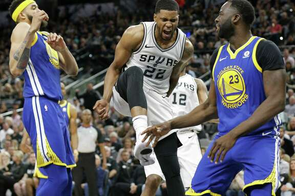 San Antonio Spurs forward Rudy Gay (22) reacts after dunking between Golden State Warriors center JaVale McGee (1) and forward Draymond Green (23) during first half action Thursday April 19, 2018 at the AT&T Center.