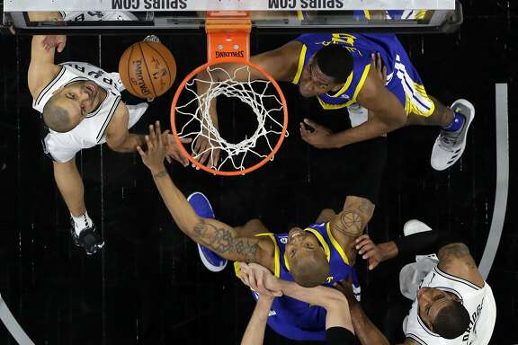 San Antonio Spurs' Tony Parker, left, takes a shot as Golden State Warriors' David West, bottom, and Kevon Looney, right, defend in the second half of Game 3 of a first-round NBA basketball playoff series in San Antonio, Thursday, April 19, 2018. Golden State won 110-97. (AP Photo/Eric Gay)