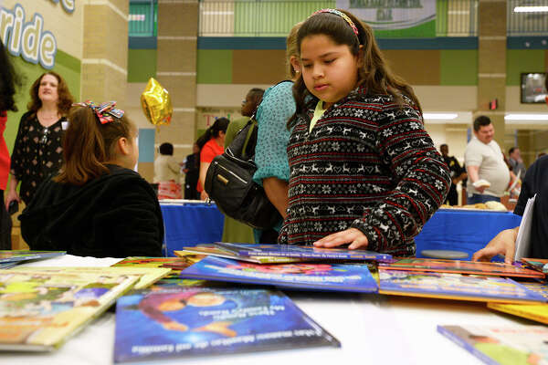 Emily Anfoso, 11, chooses books to take home at Beaumont ISD's bilingual parent resource night at South Park Middle School. The district presented information to parents on educational services and how they can help their kids learn.  Photo taken Tuesday 4/17/18 Ryan Pelham/The Enterprise