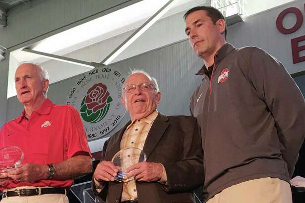 """FILE - In this April 15, 2016, file photo, former Ohio State football coach Earl Bruce is flanked by former Ohio State football coaches John Cooper, left, and Luke Fickell, at a high school coaches clinic in Columbus, Ohio. Former Ohio State football coach Earle Bruce has died at his home in central Ohio. The College Football Hall of Fame member was 87. His four daughters released a statement Friday, April 20, 2018, on the loss of """"a wonderful husband, father, grandfather and a respected coach to many.""""(AP Photo/Mitch Stacy, File)"""
