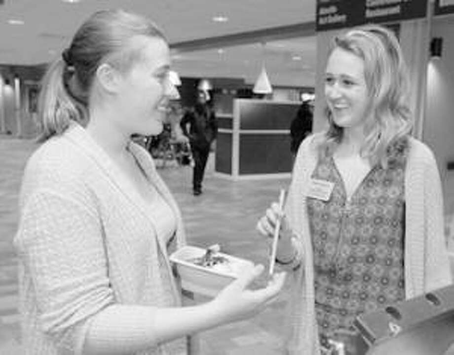 SIUE Student Government Vice President Elect Sadie Spears (right) gives a reusable straw to Lindsey Wolfford, a senior majoring in music education. Photo:       For The Telegraph