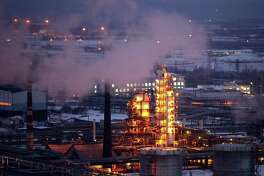 Petroleum cracking towers are seen illuminated by lights at a petroleum refinery in Russia.