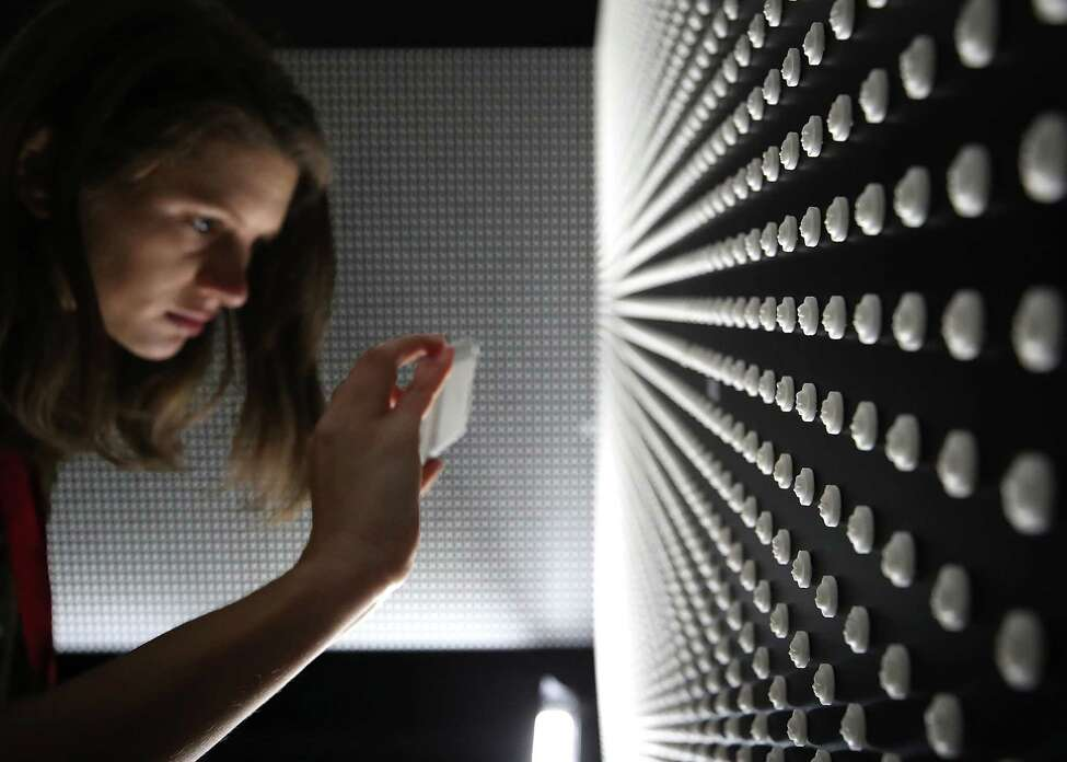 Cassie Spodak takes a picture of a memorial that consists of 22,000 engraved white pills that represent the face of someone lost to a prescription opioid overdose in 2015, at the Ellipse at President's Park, on April 11, 2018 in Washington, DC.