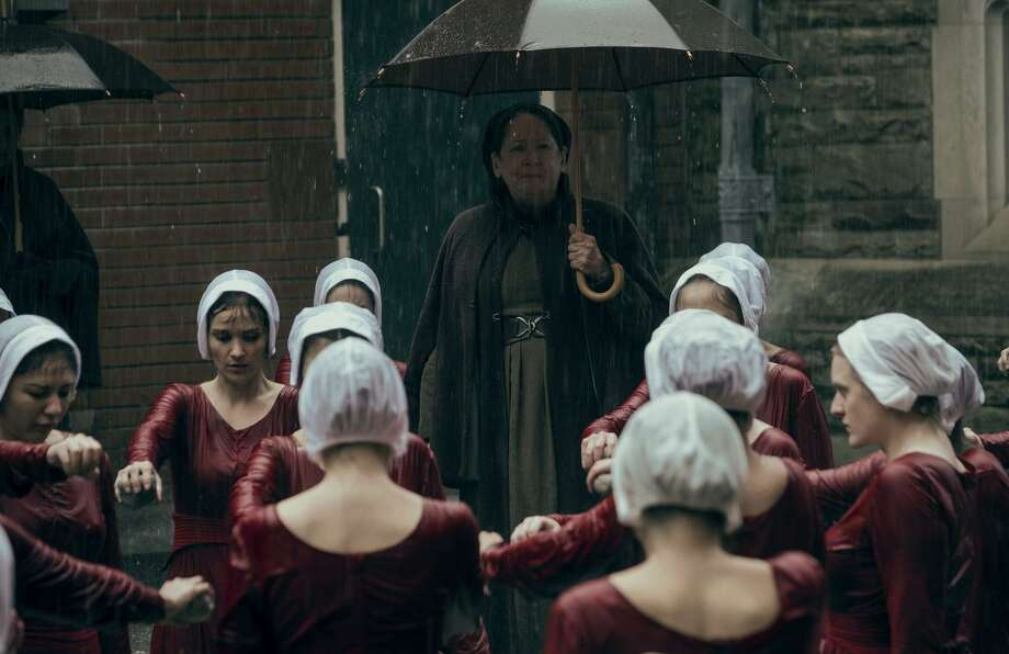 """Ann Dowd (center) stars as """"Aunt"""" Lydia, one of the older women charged with keeping the hand maids in line, in the unrelentingly dark drama about a religion-based totalitarian regime. Photo: George Kraychyk / Hulu / 2018 Hulu"""