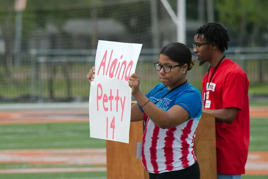 Texas City High School student Political Activism Club President Jaeden Johnson reads the name as fellow student Lauryn Bellow holds a sign with name of a victim from the Marjory Stoneman Douglas High School shooting in Parkland, FL during a walk out for school safety Friday, Apr. 20 at Texas City High School. Photo: Kirk Sides / Houston Chronicle